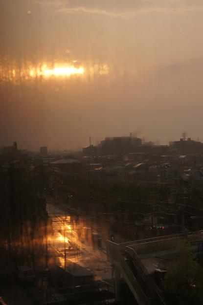 雨だれの流れる窓に西日射す